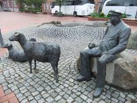 Vor dem Hotel sitzt der Schaftreiber mit seinem Hund und drei Schafen